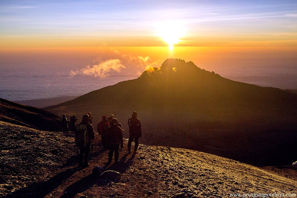 Climbers watch the sunrise from the top of Kilimanjaro mountain Tanazani